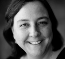 Black and white headshot photo of Sheila Smith smiling at the camera. Above should length dark dark that has a small wave, light skin.